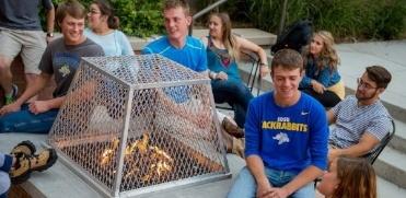 Students sitting around bonfire